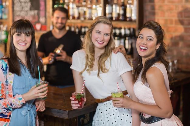 Portret van vrolijke vriendinnen die drankjes in staaf houden