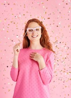 Portret van vrolijke vrouw bij confettiregen
