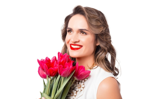 Portret van vrolijke vrouw die lacht met boeket tulpen close-up