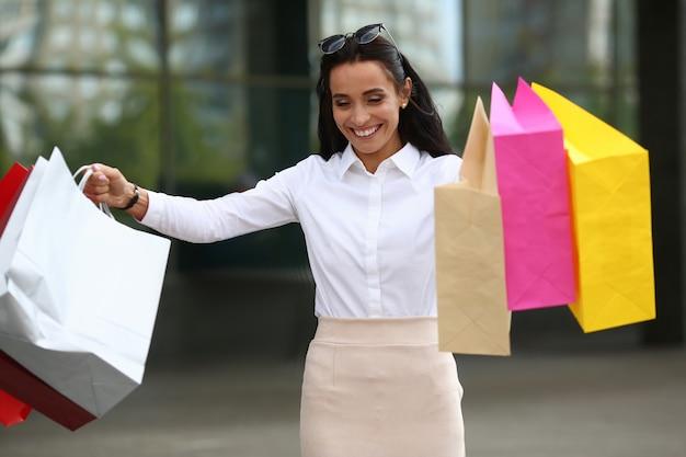 Portret van vrolijke vrouw die weg met geluk kijkt. prachtig wijfje dat kleurrijke winkelpakketten met aankopen houdt. winkelen en mode concept.