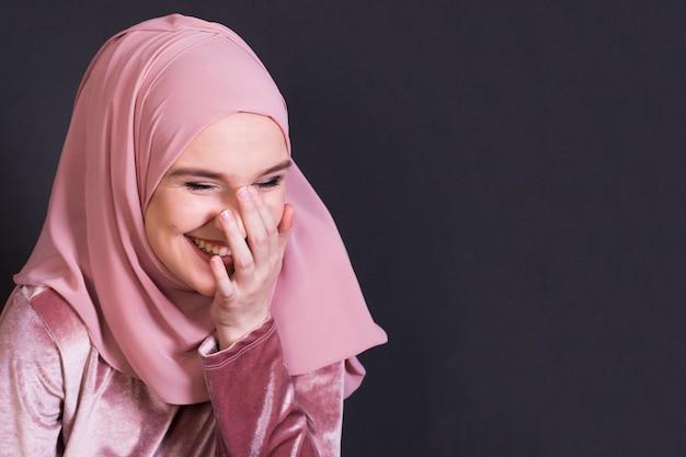 Portret van vrolijke vrouw die zich in zwarte achtergrond bevindt