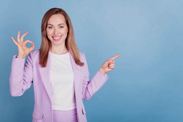 Portret van vrolijke vrouw directe vinger lege ruimte toont okey teken