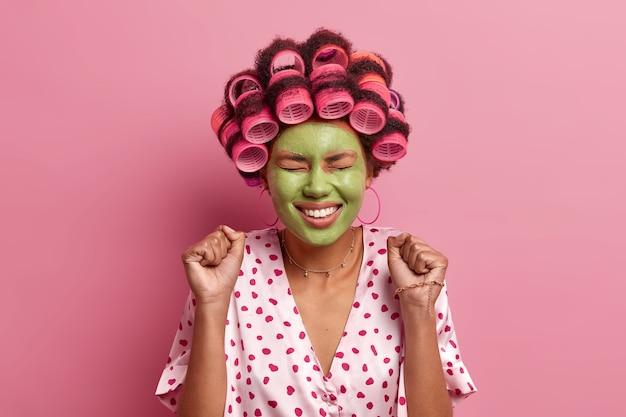 Portret van vrolijke vrouw hoort geweldig nieuws, sluit de ogen en balt vuisten, verheugt zich over positieve relevantie, draagt haarrollers en maakt kapsel, vrijetijdskleding, past schoonheidsmasker toe voor verjonging