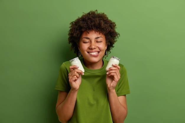 Portret van vrolijke vrouw houdt twee flessen natuurlijke zuivel yoghurt voor het ontbijt, bijt op de lippen en heeft de verleiding om te eten, staat met gesloten ogen, geïsoleerd op groene muur. gezond voedingsconcept