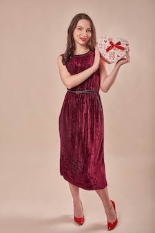 Portret van vrolijke vrouw in rode de giftdoos van de kledingsholding