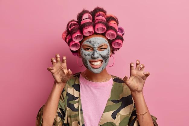 Portret van vrolijke vrouw maakt kat klauwen en gromt als een dier, draagt haarkrulspelden op het hoofd, past schoonheid kleimasker toe, gekleed nonchalant poseert tegen roze heeft grappige grimas klemt tanden