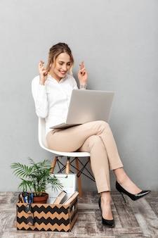Portret van vrolijke vrouw met behulp van laptop zittend in stoel met kantoor dingen, geïsoleerd