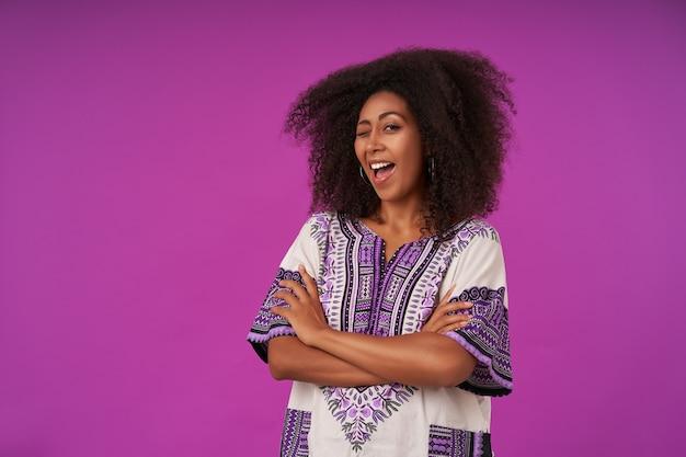 Portret van vrolijke vrouw met donkere huid en gevouwen handen breed glimlachend en knipoog geven, gekleed in wit overhemd met patronen, poseren op paars