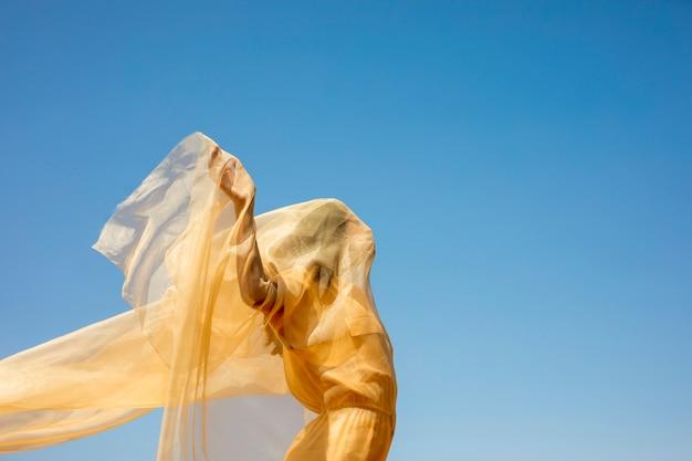 Portret van vrolijke vrouw met gele doek in de natuur