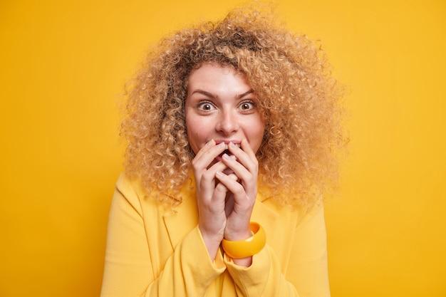 Portret van vrolijke vrouw met krullend blond haar houdt handen op mondhoort hear