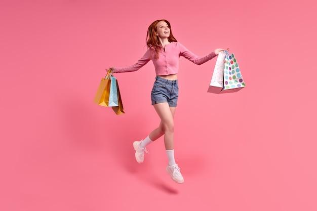 Portret van vrolijke vrouw met pakketten die hoog springen om weekendvakantie te vieren, kortingen in de winkel, zwarte vrijdag, met een casual roze shirt en denim shorts, geïsoleerd op roze