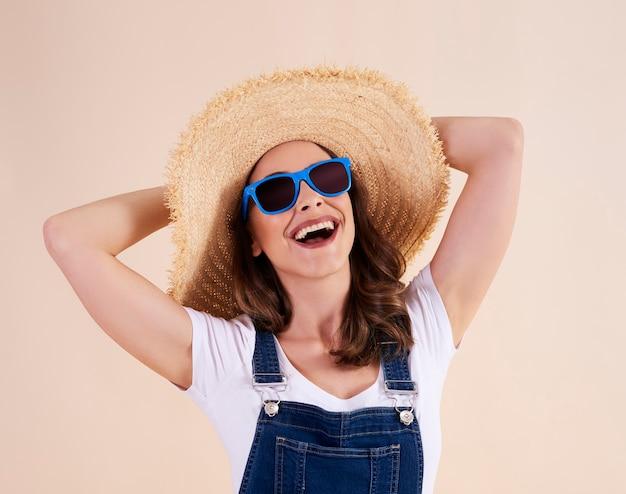 Portret van vrolijke vrouw met zonnebril en zonnehoed