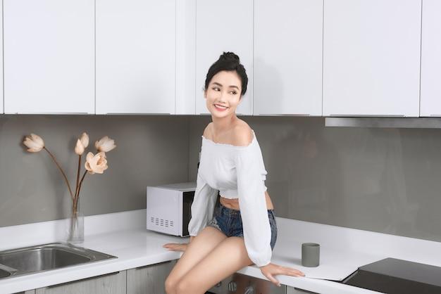 Portret van vrolijke vrouw zit op aanrecht in witte moderne keuken.