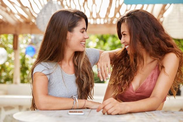 Portret van vrolijke vrouwtjes hebben plezier samen delen positief nieuws met elkaar besteden vrije tijd op terras, hebben blije uitdrukkingen.