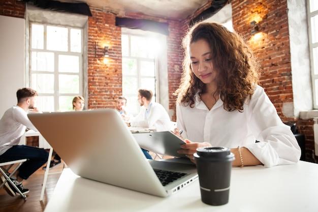 Portret van vrolijke zaken afro-amerikaanse dame die op laptop werkt.