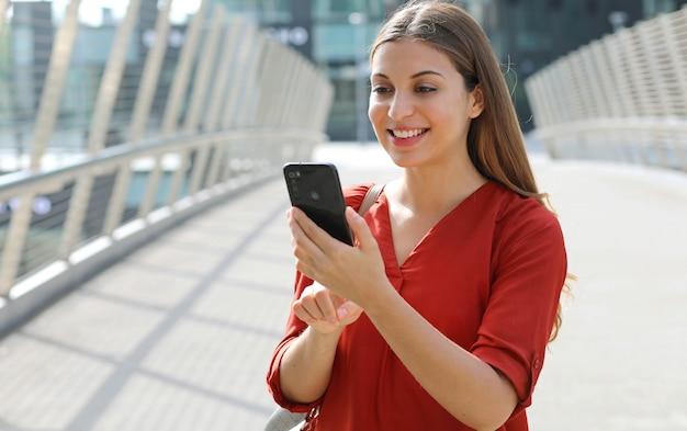 Portret van vrolijke zakenvrouw met behulp van winkelen online app op slimme telefoon in stad straat