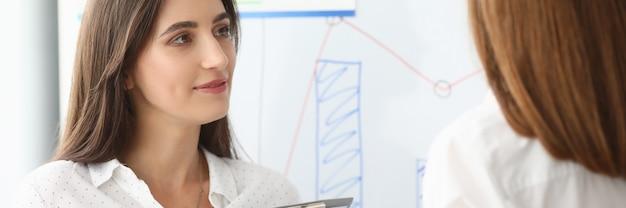 Portret van vrolijke zakenvrouw permanent op moderne werkplek en houdt belangrijke papieren tablet met grafieken en grafieken en kijkt naar iemand met kalmte. boekhoudkantoor concept