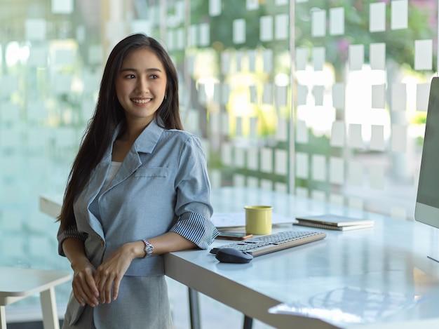 Portret van vrolijke zakenvrouw permanent op werkplek in glazen partitie kantoorruimte
