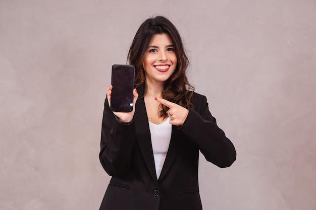 Portret van vrolijke zakenvrouw weergegeven: mobiele telefoon op leeg scherm geïsoleerd op witte achtergrond.