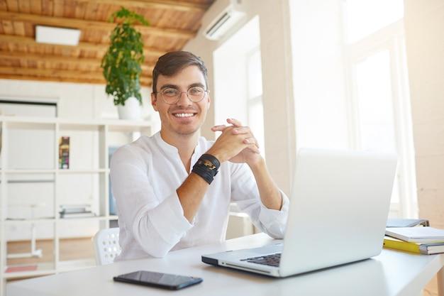 Portret van vrolijke zelfverzekerde jonge zakenman draagt een wit overhemd op kantoor