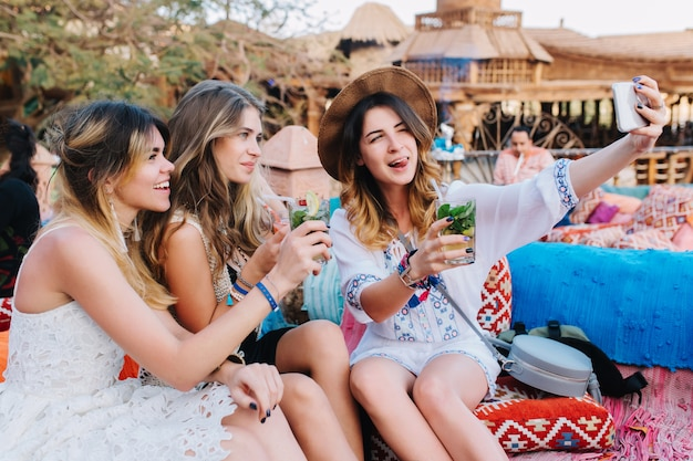 Portret van vrolijke zusters tijd samen doorbrengen in openluchtcafé en selfie maken aan de telefoon