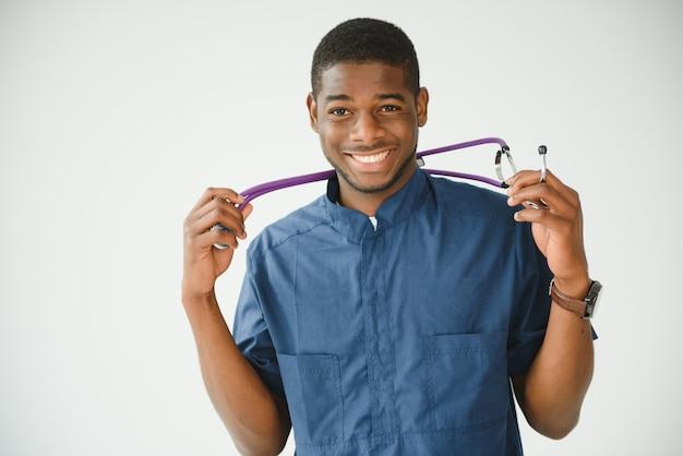 Portret van vrolijke zwarte dokter op zijn werkplek