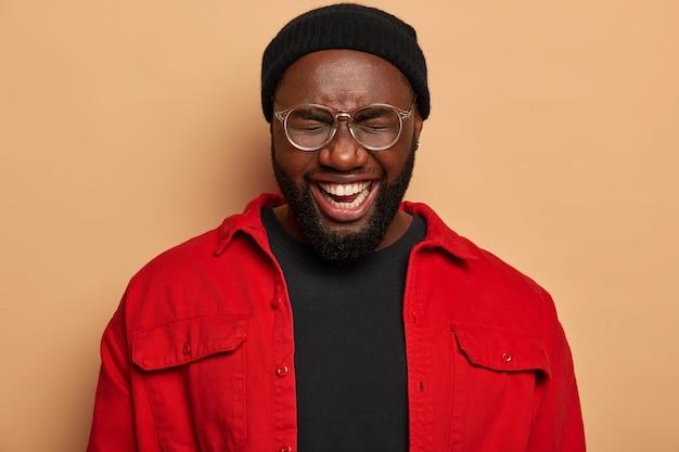 Portret van vrolijke zwarte man glimlacht toothily, loenst gezicht, poses binnen, houdt de ogen gesloten, gekleed in modieuze kleding
