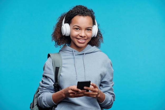 Portret van vrolijke zwarte meid in draadloze hoofdtelefoons track op smartphone kiezen tijdens het luisteren naar muziek tegen blauwe achtergrond