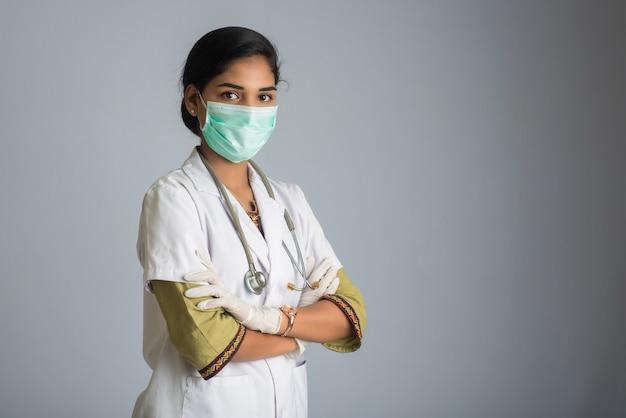 Portret van vrouw arts die een beschermend masker en handschoenen met een stethoscoop draagt. wereldepidemie van coronavirus concept.