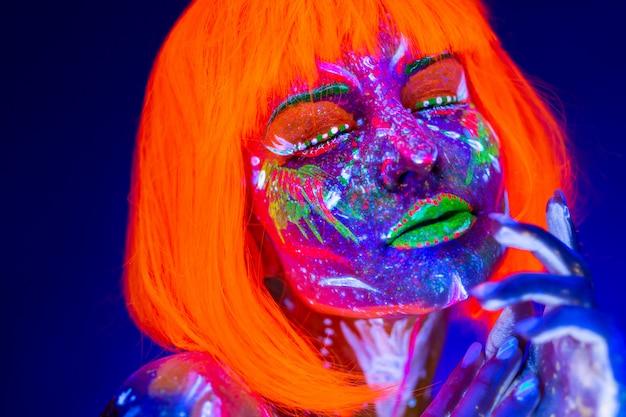 Portret van vrouw binnen met neonmake-up. fluorescerende verf in ultraviolet licht