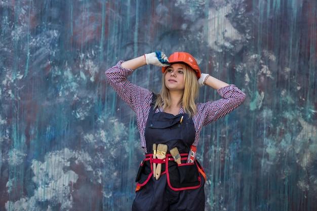 Portret van vrouw bouwer werknemer permanent dragen uniform en helmer. home renovatie.