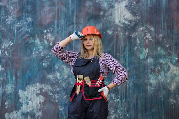 Portret van vrouw bouwer werknemer permanent dragen uniform en helmer. renovatie van het huis.
