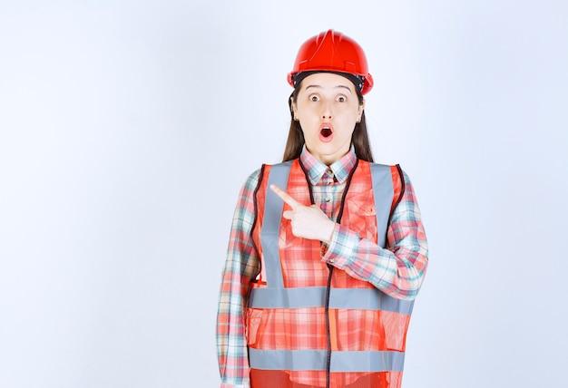 Portret van vrouw bouwvakker wijzend op witte achtergrond.