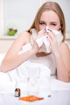 Portret van vrouw die aan koude in bed lijdt.