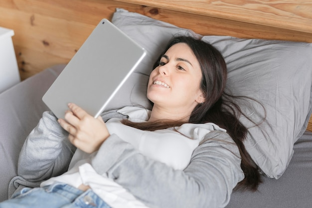 Portret van vrouw die aan tablet in bed werkt