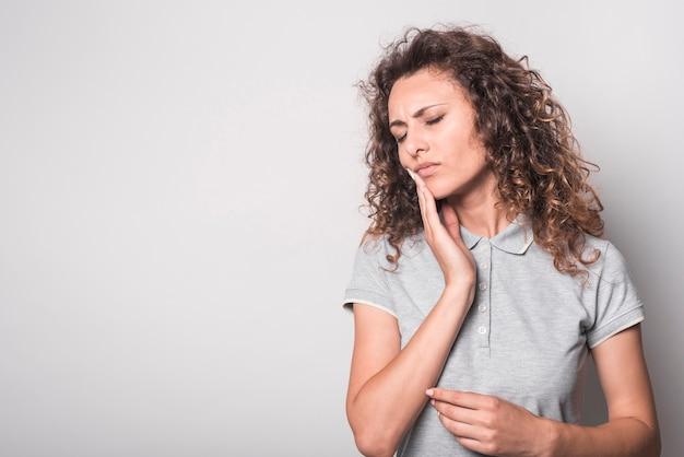 Portret van vrouw die aan tandpijn tegen witte achtergrond lijdt