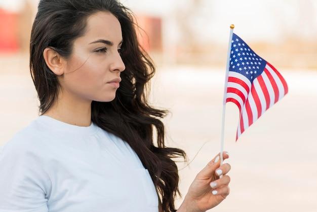 Portret van vrouw die de vlag van de vs bekijken