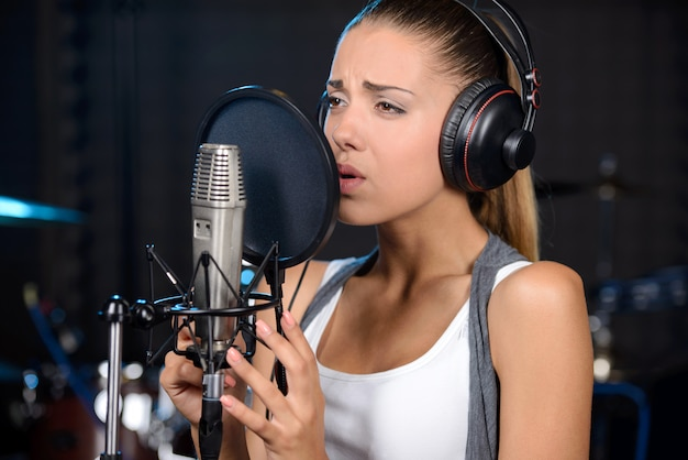 Portret van vrouw die een lied in een professionele studio opneemt