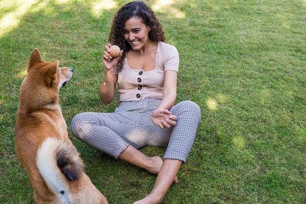 Portret van vrouw die en haar hond in de tuin koestert kust