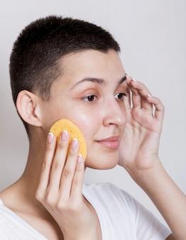 Portret van vrouw die haar gezicht behandelt