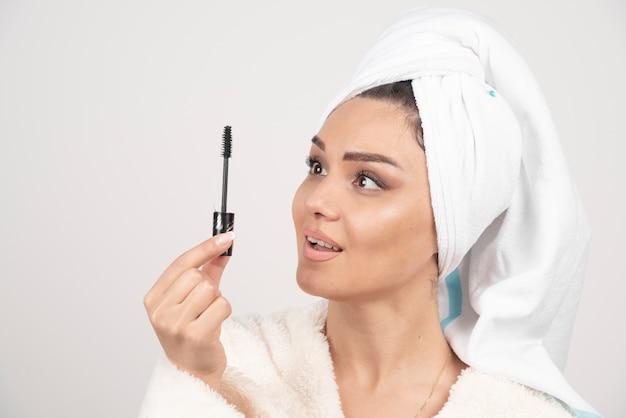 Portret van vrouw die in witte handdoek wordt verpakt die mascara bekijkt.