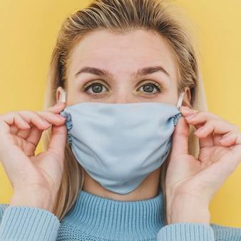 Portret van vrouw die medisch masker draagt