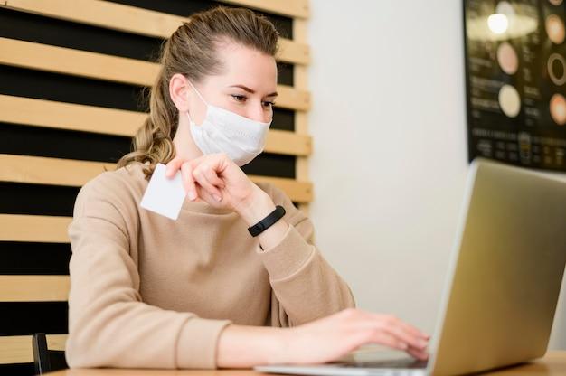 Portret van vrouw die met gezichtsmasker online winkelen
