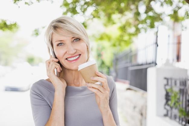 Portret van vrouw die op telefoon met koffie spreekt