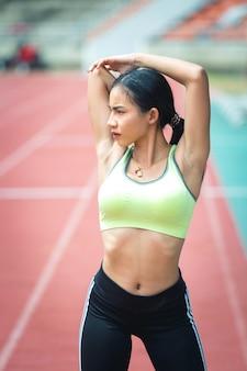 Portret van vrouw die opwarmingsoefeningen op stadion doet