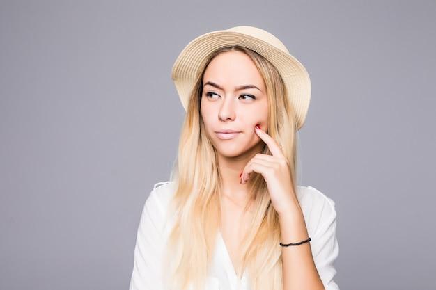 Portret van vrouw die stro dragen denken geïsoleerd over grijze muur