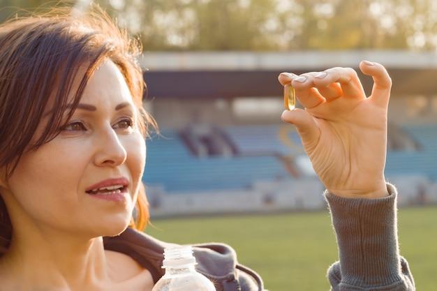 Portret van vrouw die vitamine e capsule neemt