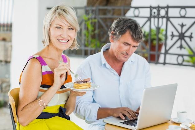 Portret van vrouw die voedsel met de mens eet die laptop met behulp van