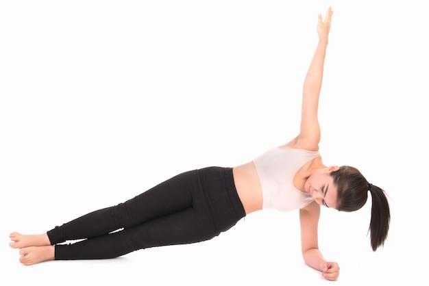 Portret van vrouw die zich uitstrekt geïsoleerd op wit. een meisje dat yoga beoefent op wit.