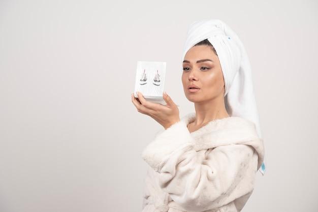 Portret van vrouw gewikkeld in witte handdoek met oogschaduw palet